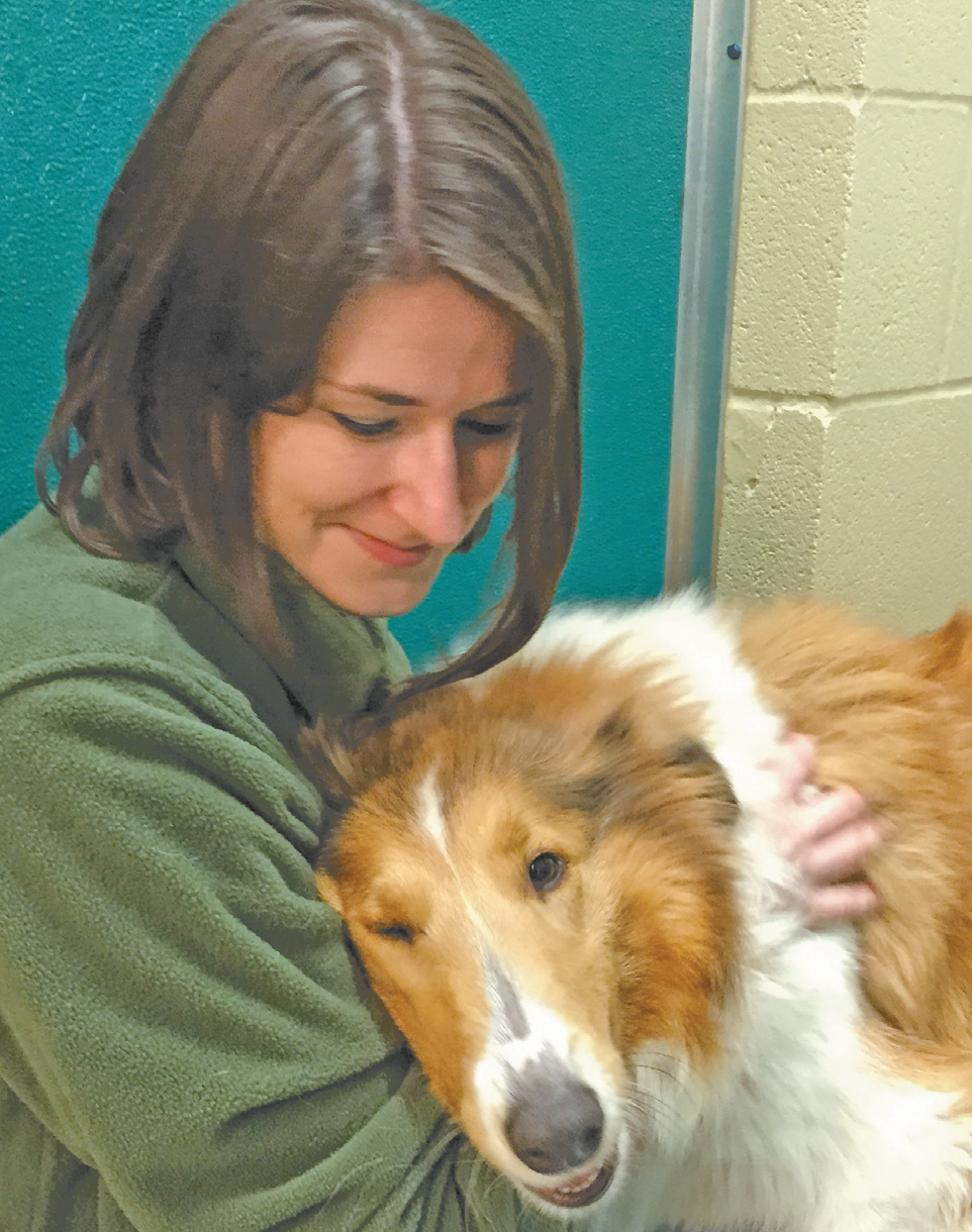 Animal Harbor Manager Amber Kelley snuggles with an adoptable dog.